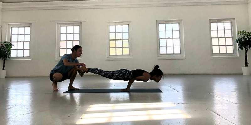 adam keen adjusting yoga student in posture